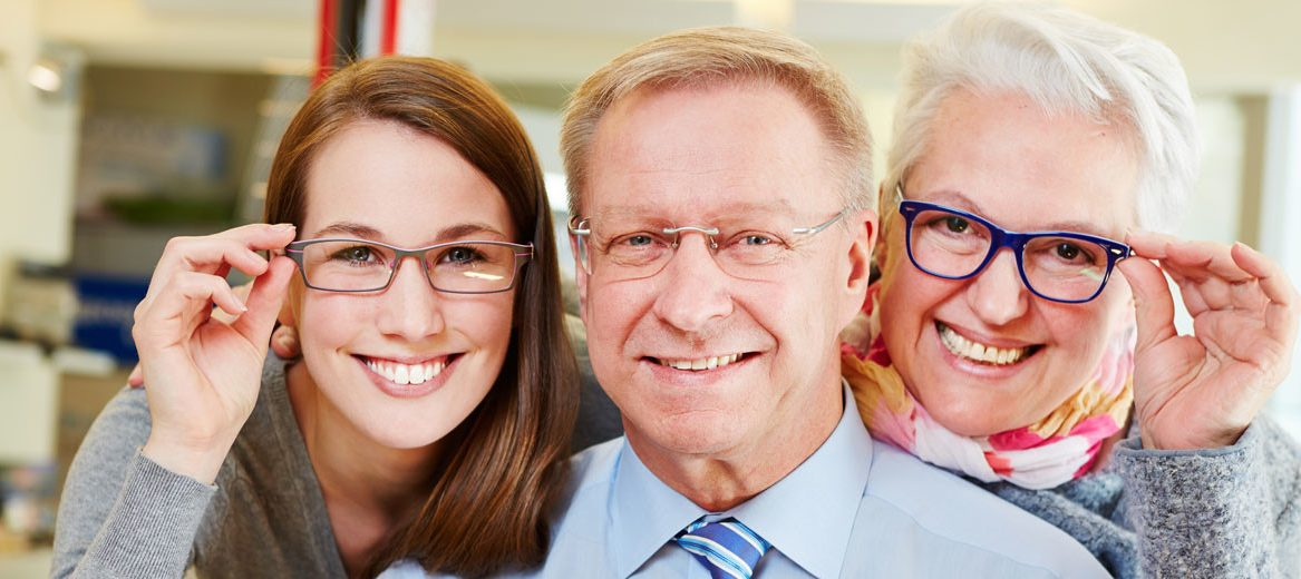 a family smiling and wearing glasses