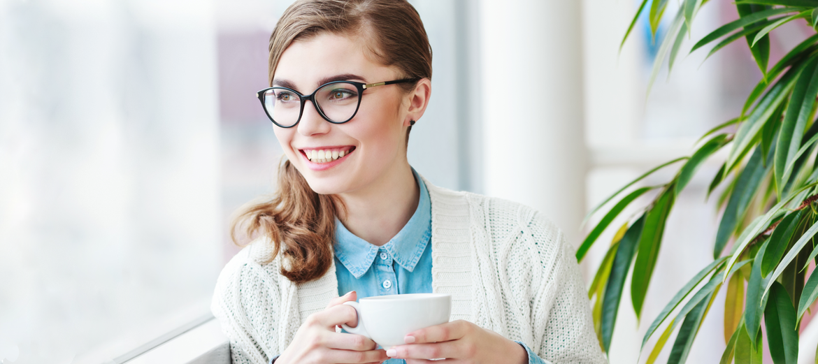 woman with nice glasses holding a cup of coffee